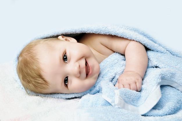 Neugeborenes kind, das im bett nach bad oder dusche sich entspannt Premium Fotos