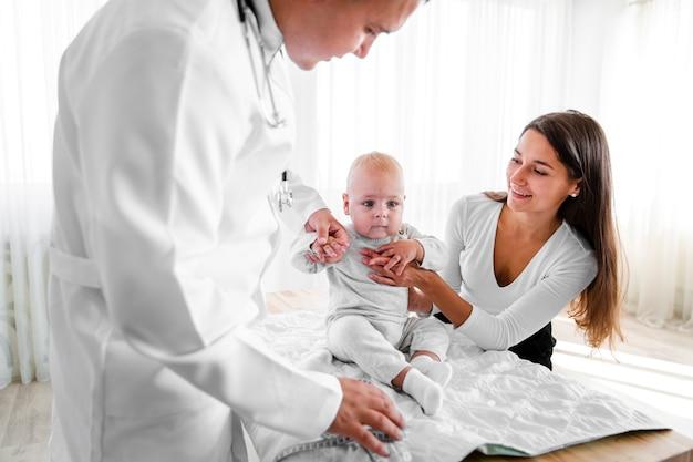 Neugeborenes von arzt und mutter gehalten Kostenlose Fotos