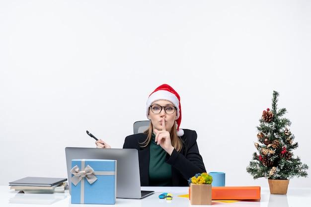 Neugierige blonde frau mit einem weihnachtsmannhut, der an einem tisch mit einem weihnachtsbaum und einem geschenk auf ihm auf weißem hintergrund sitzt Kostenlose Fotos