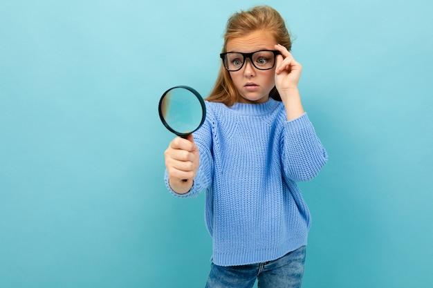Neugieriges europäisches mädchen in den gläsern schaut durch eine lupe auf hellblau Premium Fotos
