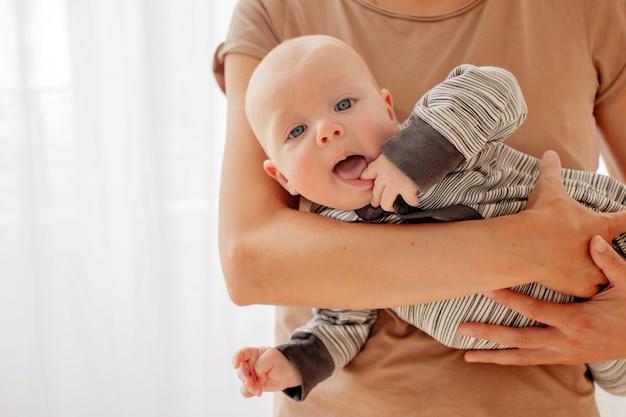 Neugieriges freches baby auf händen der mutter Premium Fotos
