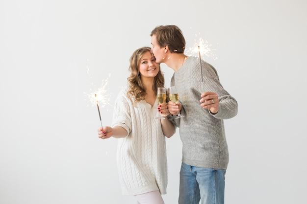 Neujahr, feiertage, datum und valentinstag-konzept - liebespaar, das wunderkerzenlicht und gläser champagner über weißer oberfläche hält Premium Fotos