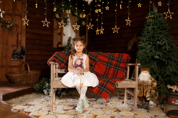 Neujahr . frohe weihnachten, schöne feiertage. ein kleines mädchen, das auf bank sitzt und puppe in den händen hält. magisches licht im nachtweihnachtsbaum-innenraum. Premium Fotos