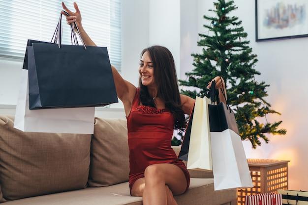 Neujahr. junge glückliche frau mit einkaufstüten zu hause Premium Fotos