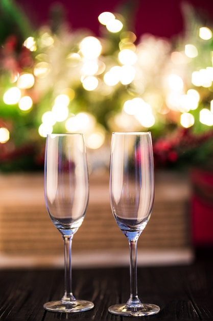 Neujahrsfeiertag oder weihnachtlicher grüner hintergrund. zweige von weihnachtsbäumen, geschmückt mit goldenen lichtern, girlanden, spielzeug und leeren champagnergläsern. nachtbeleuchtung. neujahrsgrußkonzept Kostenlose Fotos