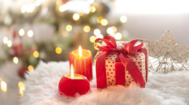 Neujahrsfeiertagshintergrund mit einer geschenkbox in einer gemütlichen atmosphäre. Kostenlose Fotos