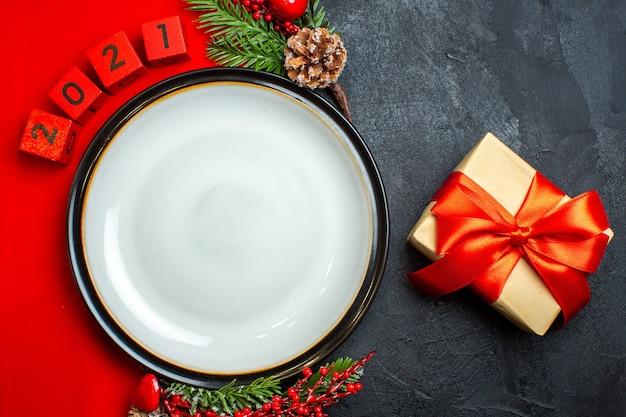 Neujahrshintergrund mit tafeltellerdekorationszubehör tannenzweigen und zahlen und geschenk auf einer roten serviette auf einem schwarzen tisch Kostenlose Fotos