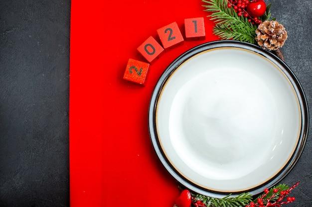 Neujahrshintergrund mit tafeltellerdekorationszubehörtannenzweigen und -nummern auf einer roten serviette auf einer horizontalen ansicht der schwarzen tabelle Kostenlose Fotos