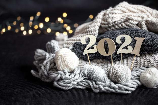 Neujahrskomposition mit gestrickten gegenständen und hölzerner neujahrszahl auf dunklem hintergrund. Kostenlose Fotos