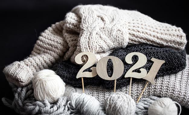 Neujahrskomposition mit gestrickten gegenständen und hölzerner neujahrszahl auf einem dunklen hintergrund schließen oben. Kostenlose Fotos
