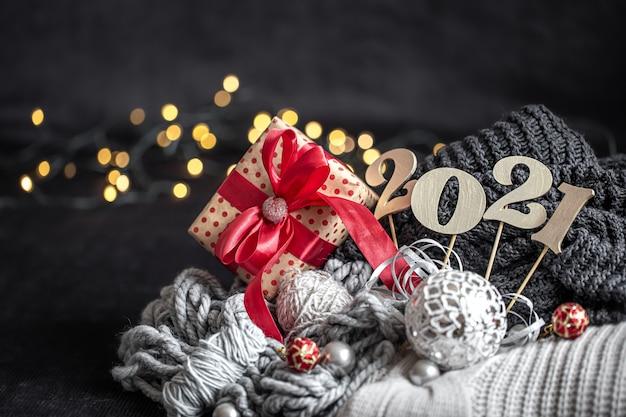 Neujahrskomposition mit hölzerner neujahrszahl und weihnachtsdekorationen auf einem dunklen hintergrund. Kostenlose Fotos