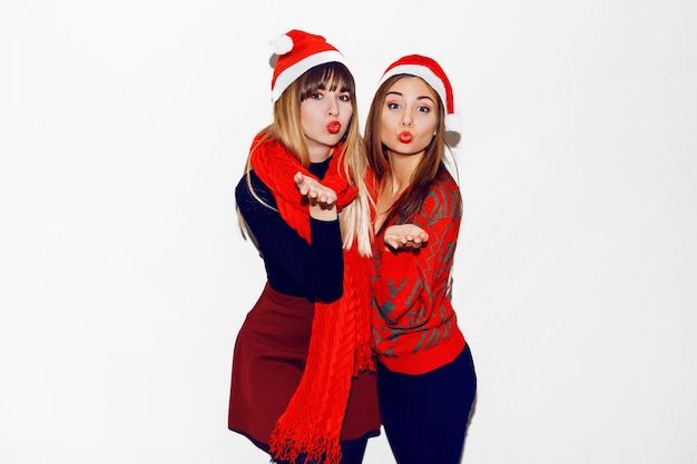 Neujahrsparty. zwei schöne mädchen in lustigen maskeraden-weihnachtsmützen senden einen kuss. innenvorrat bild der besten freunde posiert. isolieren. Kostenlose Fotos