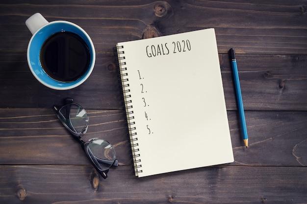Neujahrsziele, resolution oder aktionsplan 2020. hölzerne tabelle des büros mit leerem notizblock, bleistift, gläsern, telefon und tasse kaffee. Premium Fotos