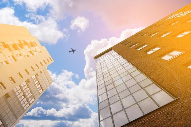 New brick mehrstöckiges gebäude auf dem hintergrund der wolken. im himmelflugzeug. getöntes foto. Premium Fotos