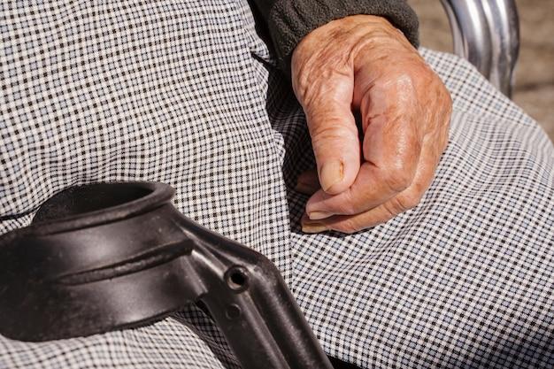Nicht erkennbare alte frau, die mit hilfe einer krücke sitzt. lebensstil älterer menschen mit behinderungen. kinderheimkonzept für rentner. altenheim für altenpflege. Premium Fotos