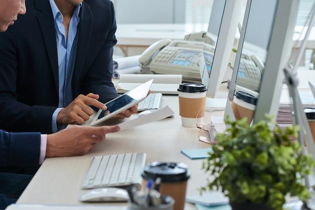 Nicht erkennbare geschäftsmänner, die am schreibtisch sitzen und zusammen tablette und dokument betrachten Kostenlose Fotos