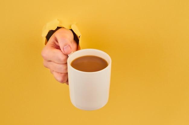 Nicht erkennbare person, die kaffeetasse auf orange hintergrundnahaufnahme hält Premium Fotos
