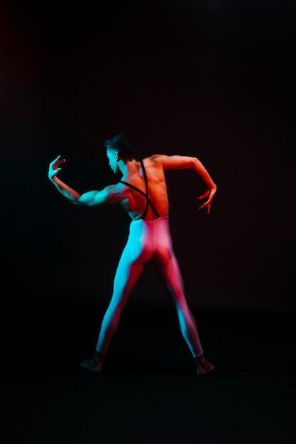 Nicht erkennbarer balletttänzer im trikotanzug mit gebogenen armen im scheinwerferlicht Kostenlose Fotos
