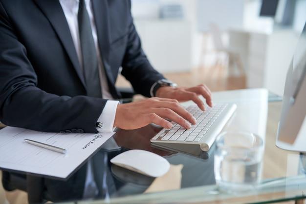 Nicht erkennbarer geschäftsmann, der auf tastatur im büro schreibt Kostenlose Fotos
