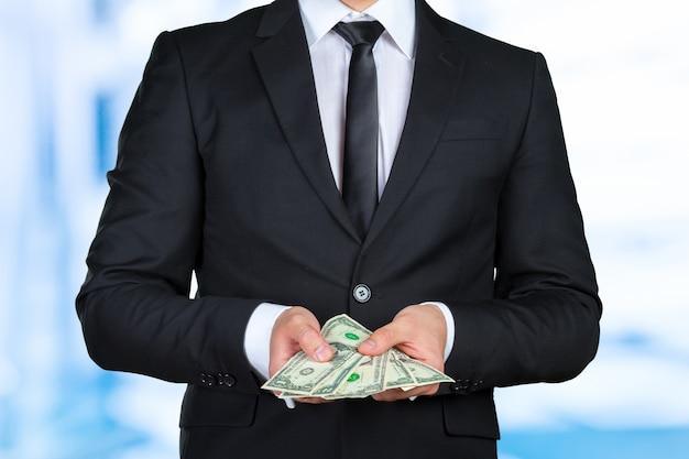 Nicht erkennbarer geschäftsmann zeigt dollarbanknote Premium Fotos