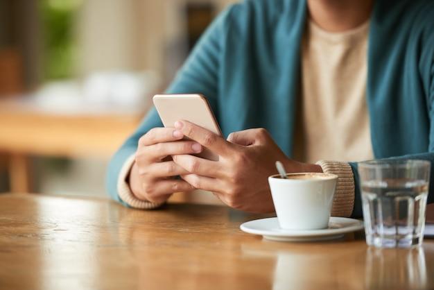 Nicht erkennbarer mann, der im café mit tasse kaffee und wasser sitzt und smartphone verwendet Kostenlose Fotos