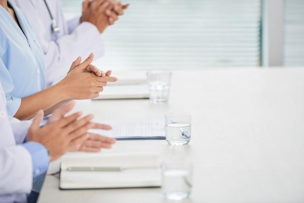 Nicht wiedererkennbare ärzte, die auf der konferenz mit notizbüchern und wasser in gläsern sitzen und applaudieren Kostenlose Fotos