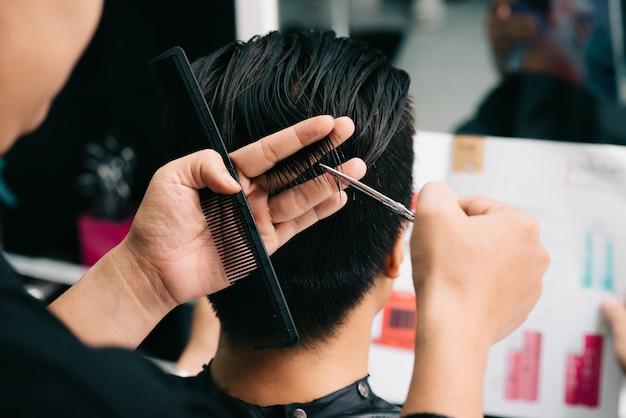 Nicht wiedererkennbarer friseur, der das haar des kunden mit kamm und scheren im salon schneidet Kostenlose Fotos