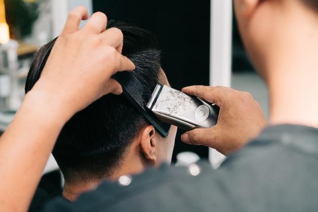 Nicht wiedererkennbarer friseur, der dem kunden die haare mit trimmer und kamm schneidet Kostenlose Fotos
