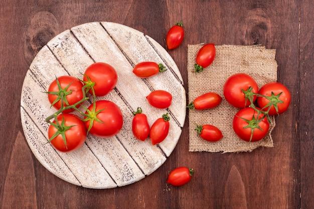 Niederlassungen von kirschtomaten auf hölzernem brett nahe den tomaten auf sackleinen auf hölzernem Kostenlose Fotos