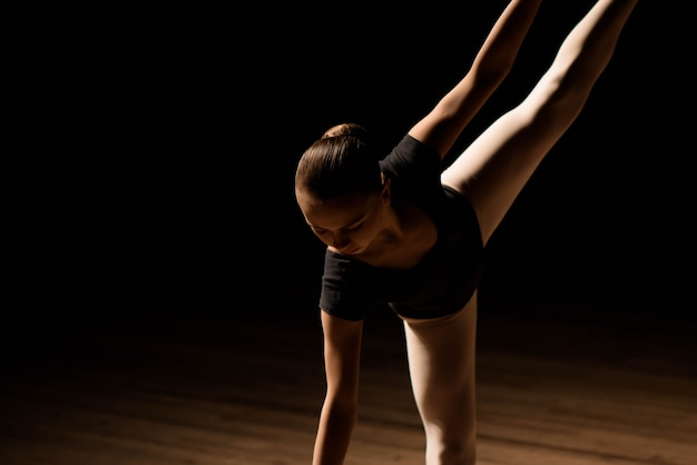 Niedliche kleine ballerina im dunklen ballettkostüm tanzt auf der bühne. kind in der tanzklasse. mädchen studiert ballett. Premium Fotos