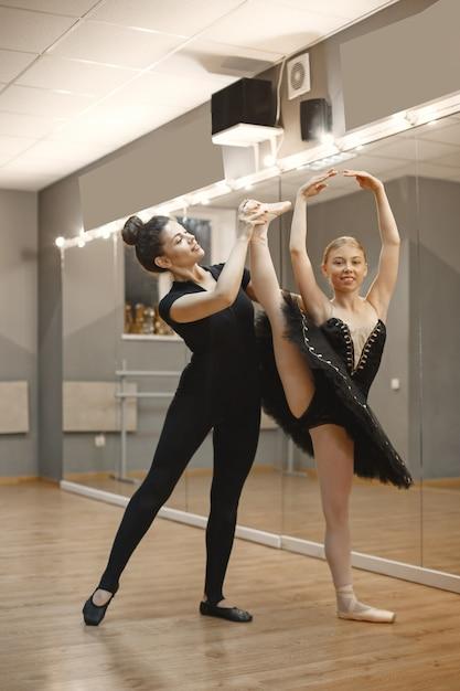 Niedliche kleine ballerina im schwarzen ballettkostüm. junge dame tanzt im raum. mädchen in der tanzklasse mit lehrer. Kostenlose Fotos
