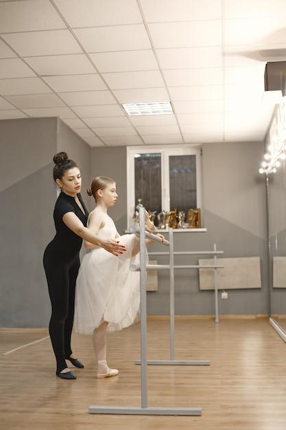 Niedliche kleine ballerina im weißen ballettkostüm. junge dame tanzt im raum. mädchen in der tanzklasse mit lehrer. Kostenlose Fotos