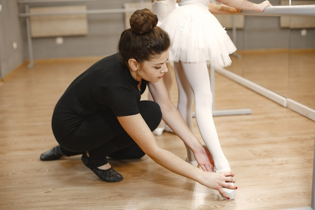 Niedliche kleine ballerinas im rosa ballettkostüm. kinder in spitzenschuhen tanzen im raum. kind im tanzkurs mit lehrer. Kostenlose Fotos