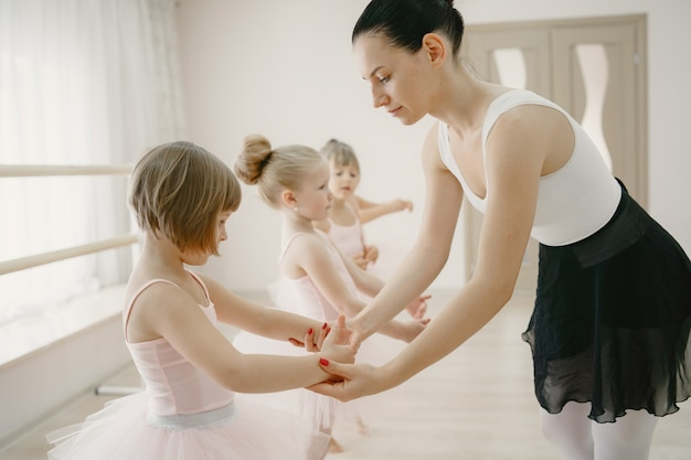 Niedliche kleine ballerinas im rosa ballettkostüm. kinder in spitzenschuhen tanzen im raum Kostenlose Fotos
