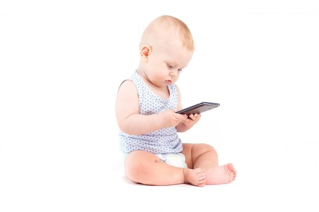 Niedliches hübsches baby im blauen hemd und windel halten mobiltelefon Premium Fotos