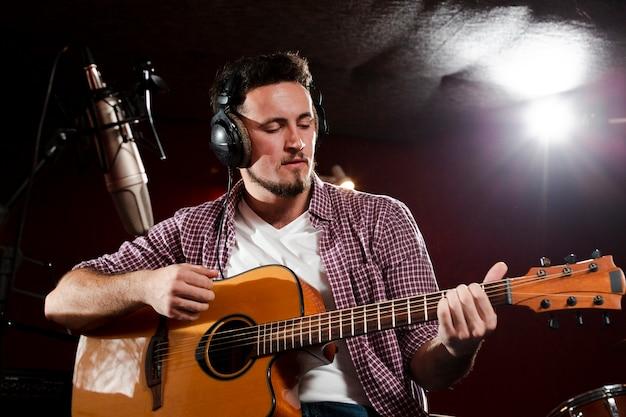 Niedrige ansicht schoss von einem mann, der gitarre spielt und kopfhörer trägt Kostenlose Fotos