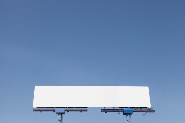 Niedrige winkelsicht der werbungsanschlagtafel gegen blauen klaren himmel Kostenlose Fotos