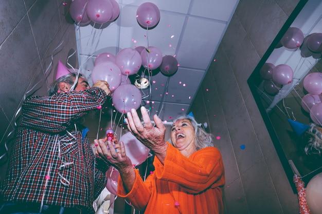 Niedrige winkelsicht des älteren glücklichen paars die konfetti in der party werfend Kostenlose Fotos