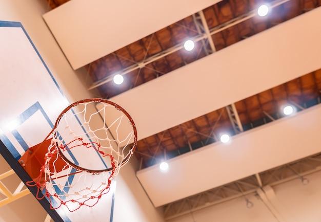 Niedrige winkelsicht des basketballkorbes in der turnhalle mit deckenscheinwerfer, Premium Fotos