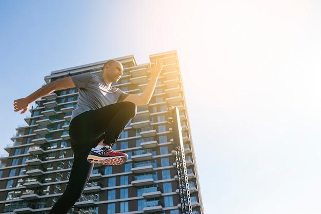 Niedrige winkelsicht des männlichen rüttlers laufend vor gebäude gegen blauen himmel Kostenlose Fotos