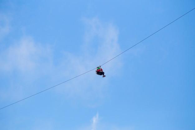 Niedrige winkelsicht des touristen eine ziplinie abenteuer gegen blauen himmel reiten Kostenlose Fotos