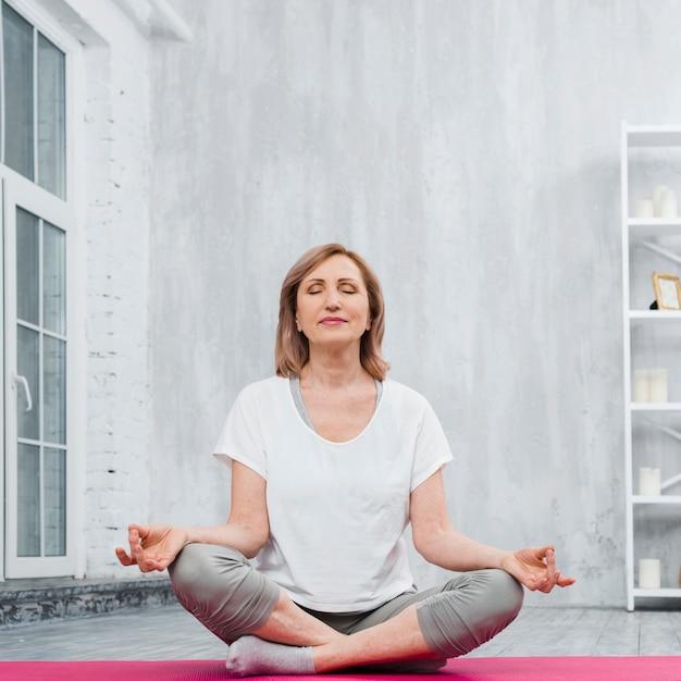 Niedrige winkelsicht einer älteren frau, die zu hause meditation tut Kostenlose Fotos