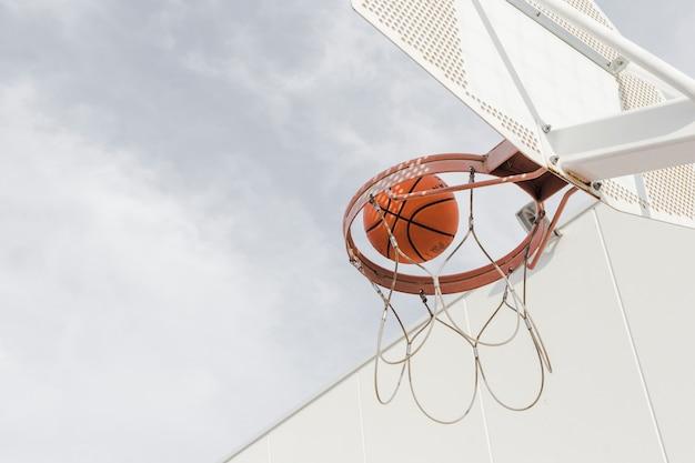 Niedrige winkelsicht eines basketballs, der durch band fällt Kostenlose Fotos