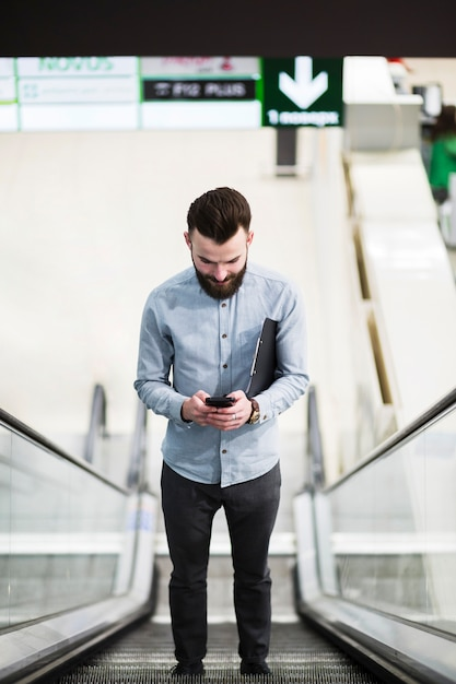 Niedrige winkelsicht eines jungen geschäftsmannes, der auf rolltreppe unter verwendung des handys steht Kostenlose Fotos