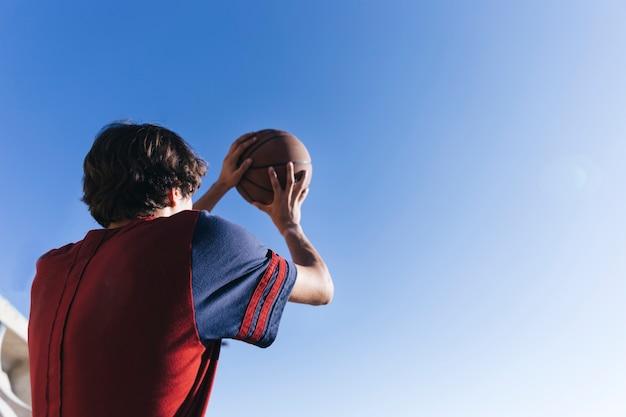 Niedrige winkelsicht eines teenagers, der basketball gegen blauen himmel hält Kostenlose Fotos
