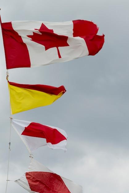 Niedrige winkelsicht von flatternden flaggen am hummer-bucht-hauptleuchtturm, gros morne national park, newfou Premium Fotos