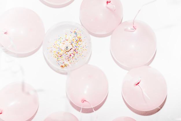 Niedrige winkelsicht von geburtstagsballonen mit ausläufern auf weißem hintergrund Kostenlose Fotos