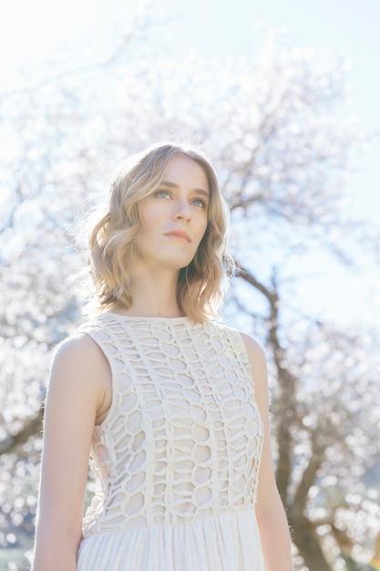Niedrige winkelsichtfrau im weiß unter sonnenlicht Kostenlose Fotos