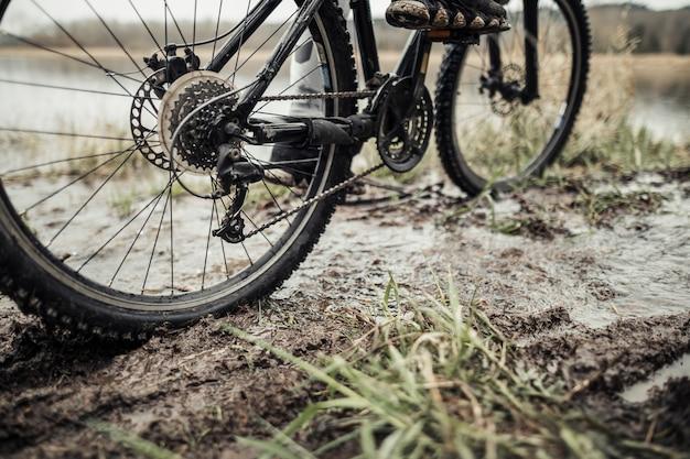 Niedriger abschnitt der füße des radfahrers auf fahrrad im schlamm Kostenlose Fotos