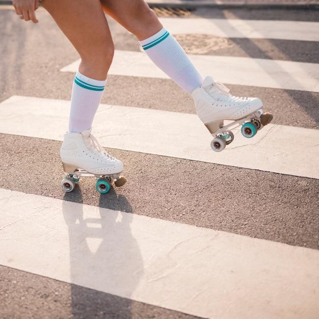 Niedriger abschnitt des weiblichen schlittschuhläufers eislaufend auf zebrastreifen Kostenlose Fotos